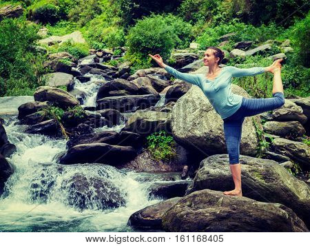 Woman doing yoga asana Natarajasana - Lord of the dance pose outdoors at waterfall in Himalayas. Vintage retro effect filtered hipster style image.