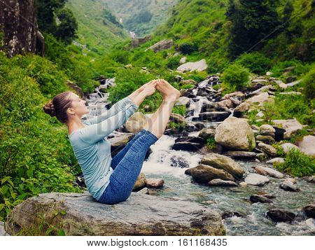 Yoga exercise outdoors -  woman doing Ashtanga Vinyasa Yoga balance asana Ubhaya padangusthasana Big Double Toe Yoga Pose at waterfall in Himalayas in India. Vintage retro hipster style image.