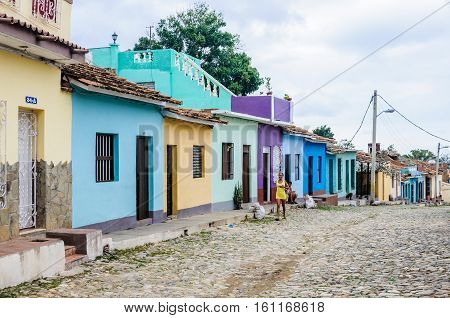TRINIDAD, CUBA - MARCH 23, 2016: Girl approaching on the cobblestone streets in the UNESCO World Heritage old town of Trinidad Cuba