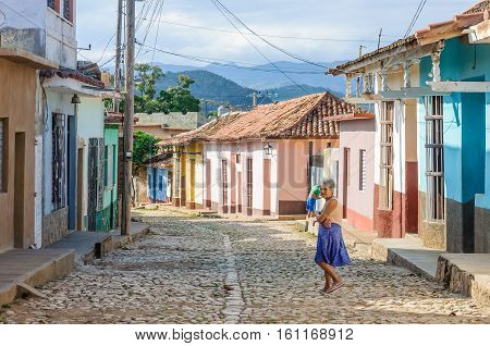 TRINIDAD, CUBA - MARCH 23, 2016: Local woman in front of colorful houses on the cobblestone streets in the UNESCO World Heritage city center of Trinidad Cuba