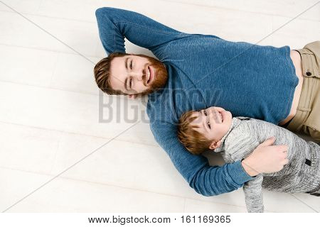Photo of young father dressed in blue sweater lies on floor with his little cheerful son in room indoors
