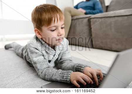 Photo of little cute child using laptop while lies in floor indoors. Look at laptop.
