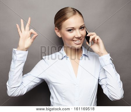 lifestyle, business  and people concept: Portrait of smiling business woman phone talking and show OK