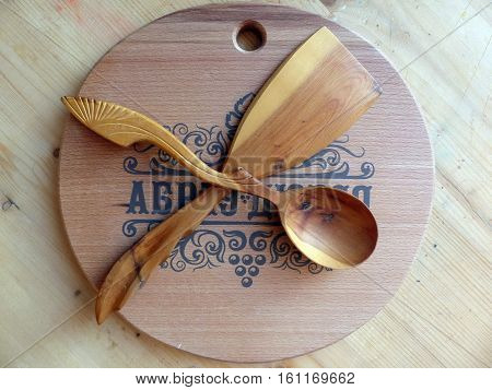Wooden spoon, kitchen spatula made of Karelian birch. Cutting board. Handmade. Russian folk crafts. Vaalam. Close-up