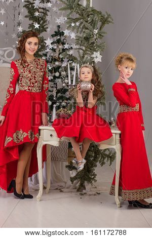 Three girls in a red evening dress the Christmas tree. Beautiful girlfriend in the anticipation of Christmas.