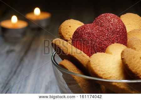heart in a vase among biscuit on the background of candles. Valentine's Day