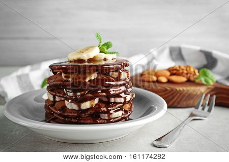 Tasty pancakes with banana and chocolate sauce on plate