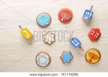 Tasty glazed cookies and dreidels for Hanukkah on light wooden table