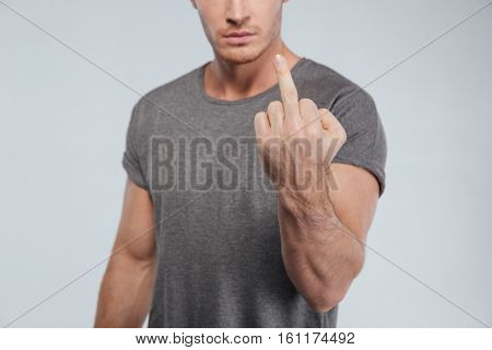 Cropped image of a young serious man showing fuck sign over white background