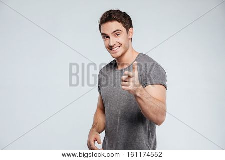 Portrait of smiling brunette man pointing finger at camera isolated on the gray background