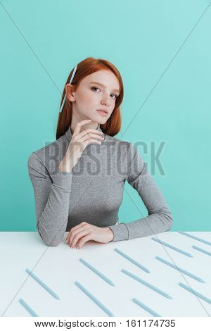 Beautiful young woman with pencil behind ear sitting at the table over blue background