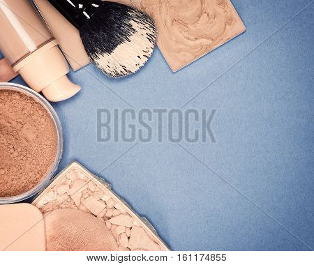 Foundation makeup products with brush and cosmetic sponges. Copy space. Vintage toning