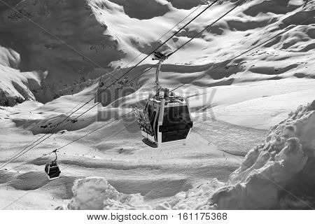 Black and white view on ski lift in snow mountains. Ski slopes of Mount Elbrus Caucasus Mountain in winter.