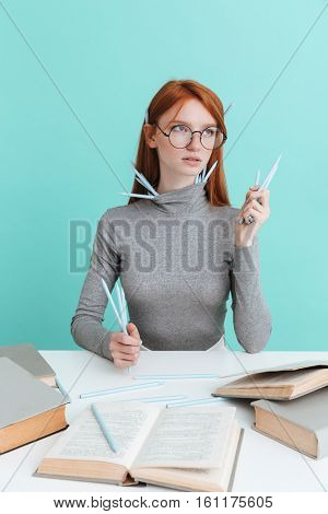 Pretty redhead young woman in round glasses with pencils sitting and reading over blue background