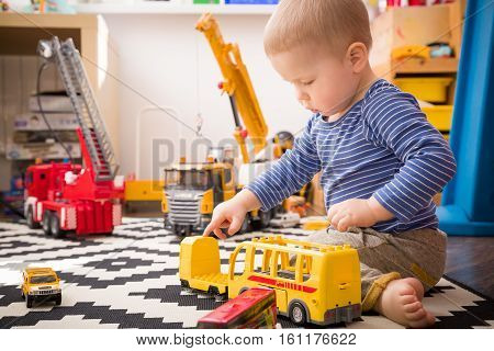 Cute little baby boy playing with toy school bus in his room. Indoors activities with children. Child playing in kid's room.
