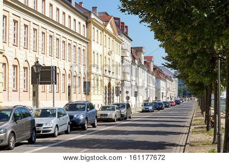 POTSDAM, GERMANY - AUGUST 27 2016: Cars sit in front of a row of historic buildings along tree-lined Yorckstrasse in Potsdam, Germany.
