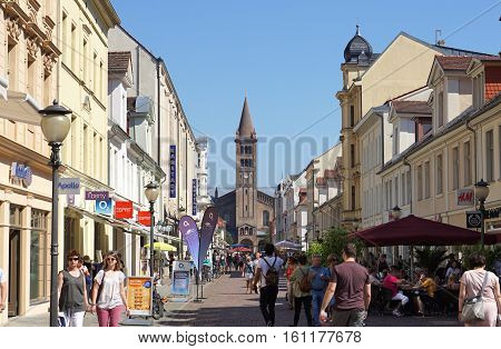 POTSDAM, GERMANY - AUGUST 27 2016: Pedestrians walk along Potsdam's crowded shopping street, Brandenburger Strasse. The pedestrianised road leads towards the Roman Catholic Priory Church of St Peter and St Paul.