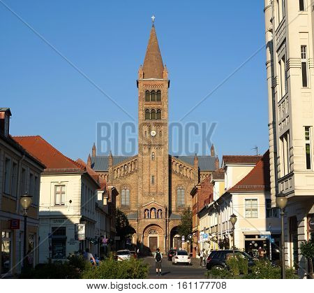 POTSDAM, GERMANY - AUGUST 27 2016: Pedestrians and cyclists travel along Brandenburger Strasse in Potsdam, Germany in the late afternoon. At the end of the street is the historic Church of St Peter and Paul.