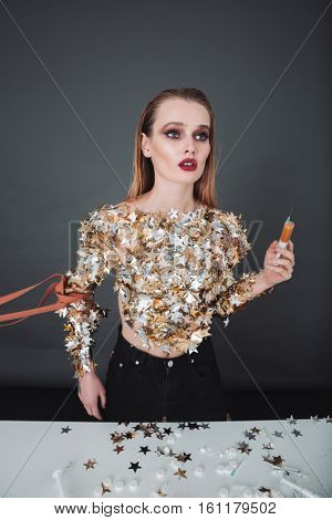 Beautiful addicted young woman with stars on her body holding syringe with drugs