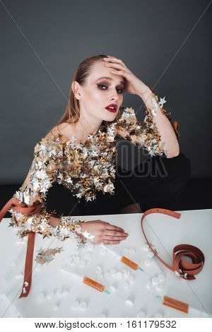 Addicted young woman sitting at the table with syringes and pills