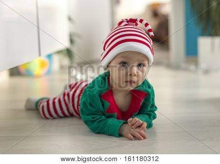 child in a Santa's helper elf costume lying on the floor