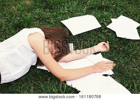 Business Woman Lying On Grass Beside Paper