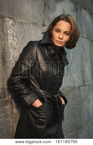 Beautiful young woman in leather raincoat near stone wall