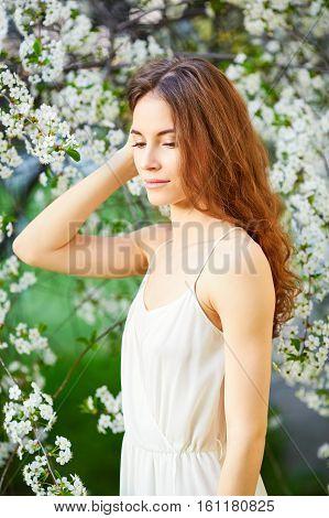 Young Beautiful Woman In White Dress Enjoying Of Blooming Tree