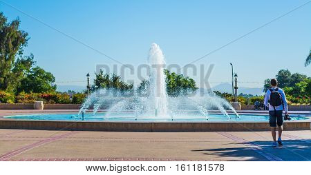 Photographer walking by a fountain in Balboa park San Diego