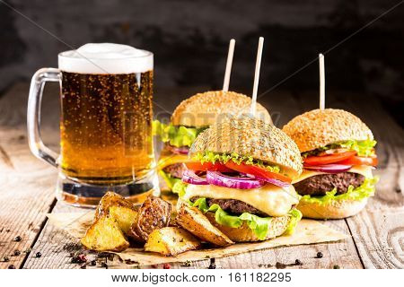 homemade burgers with beef and fried potatoes and glass of cold beer on wooden table on a dark background