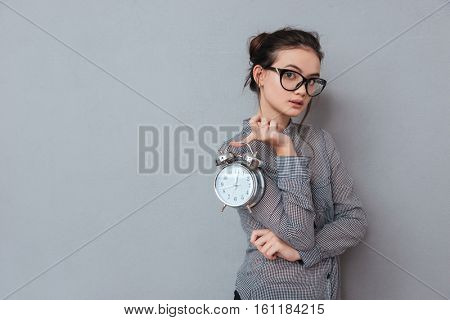 Asian cute woman in glasses and shirt posing with clock in hand. Isolated gray background