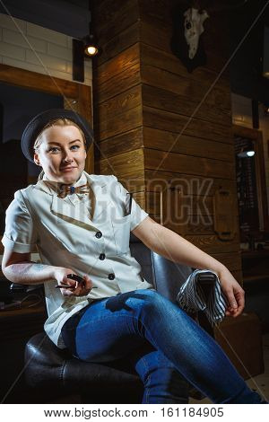 Portrait of fashion woman barber hairstylist with straight razor in hand in the barbershop