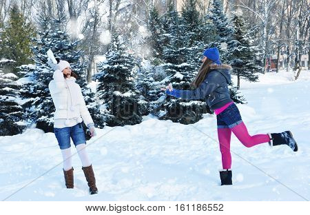 Two girls in winter throw oneself snow. Sunny winter day