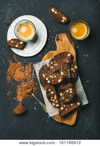 Dark chocolate and sea salt Biscotti with almonds and two glasses of coffee espresso on vintage wooden serving board over dark stone background, top view, vertical composition