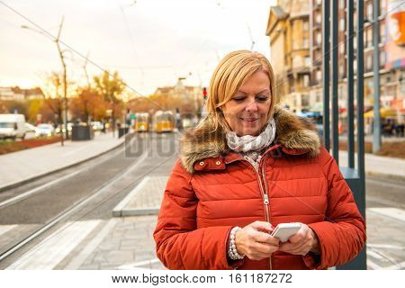 A nice middle age woman standing in front of a tram station in a winter jacket and using her smartphone