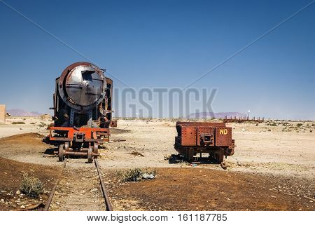 Photo of large iron machine on railway surrounded by lonely plain near Salar de Uyuni in Bolivia.