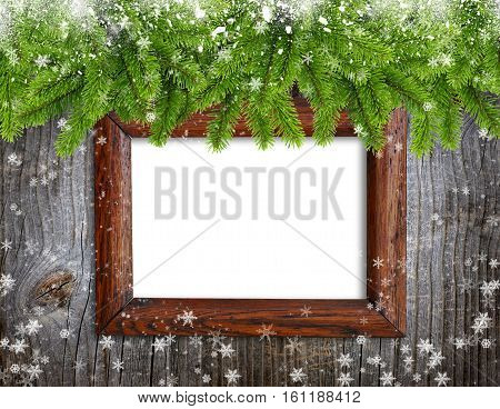 Old frame with snowbound branches of spruce on wooden background