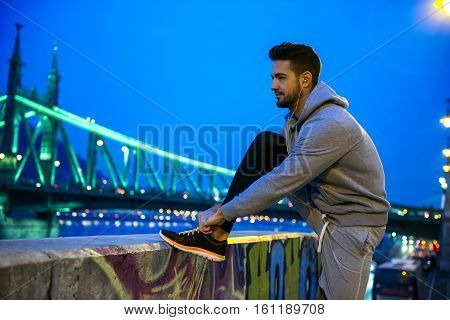 A handsome young sportsman ties his shoelace on the street at night on the riverside with a bridge behind him