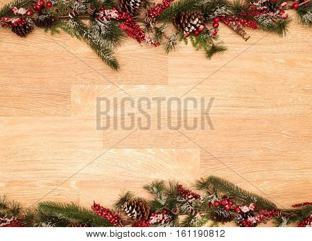Christmas or Xmas Holiday background on old plank wood with fir branches, red berries, pine cones and snow
