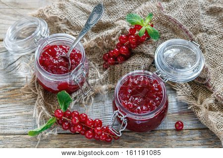 Jars Of Jam Red Currant, Green Mint And Old Sacking.
