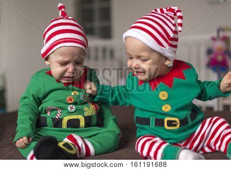 Aggressive children elf helper in Santa costume are fighting