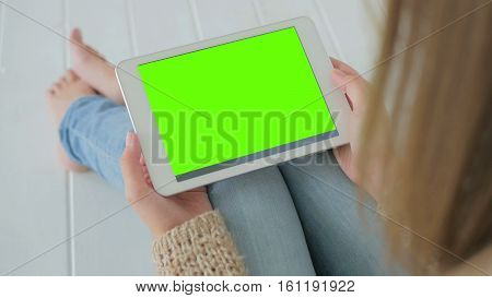 Woman sitting on the white wooden floor and looking at horizontal tablet computer with green screen. Close up shot of woman's hands with pad
