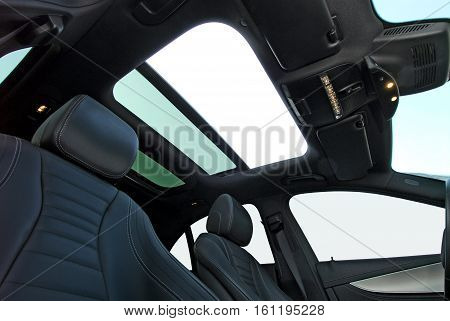 photo large sunroof inside car, sky and clouds