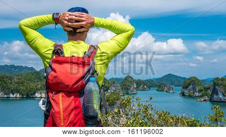 Traveler with Backpack enjoy the View over Roks in Kabui Bay near Waigeo. West Papuan, Raja Ampat. Indonesia