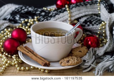 Horizontal photo of hot green tea in a white mug with spoon cinnamon sticks chocolate cookies knitted blanket and christmas decoration