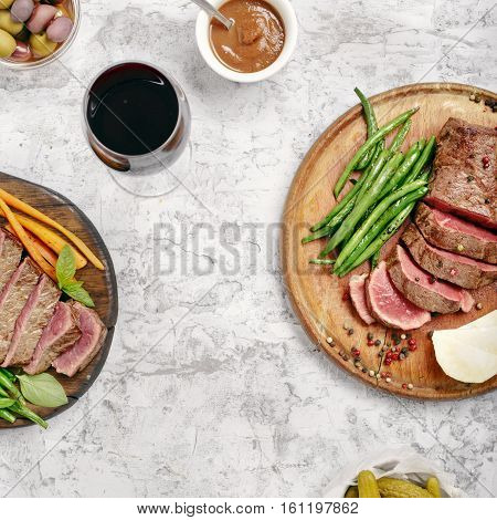 Steak with side dish of French beans and glass of red wine on a wooden board on rough white surface top view