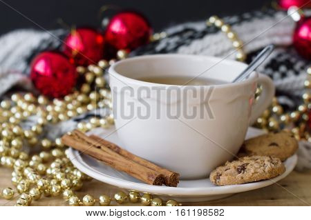 Green tea with cinnamon and chocolate cookies and christmas decoration. Red christmas ball golden chain with beads and knitted blanket. Christmas breakfast