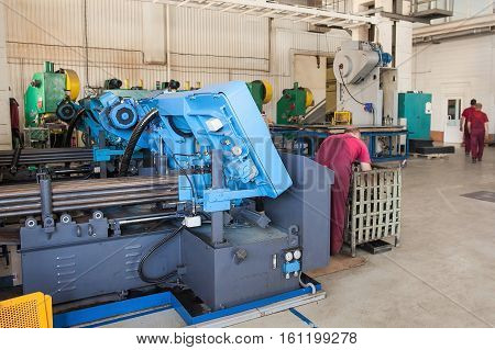metal laser cutting machine operator working in factory. the specialist stand near the modern laser machine at factory on production of metal details.