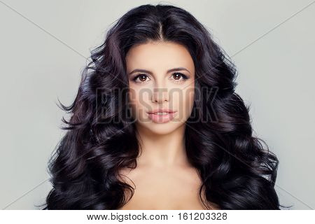 Healthy Woman with Clear Skin and Long Curly Hair. Perfect Face and Hairstyle. Skincare and Haircare Concept