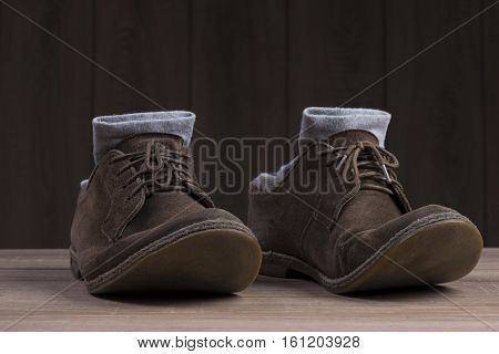 Brown suede shoes with brown laces and grey socks on the background of dark natural wood.